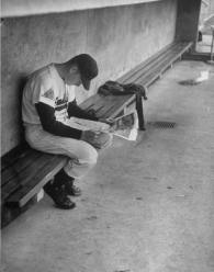 Baseball player Billy Joe Davidson sitting alone in the dugout reading a newspaper before a game